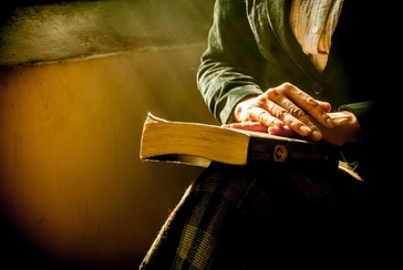 Mature woman sitting with hands on top of a book