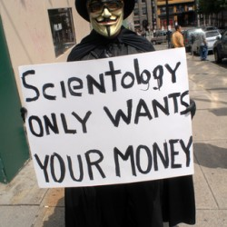 Protester in cloak with banner saying 'Scientology only wants your money!'